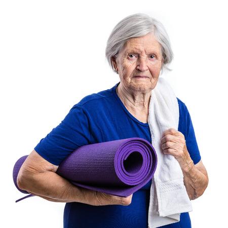mature women: Senior woman holding yoga mat over white