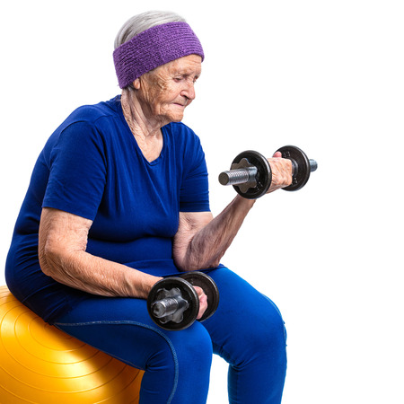 adult 80s: Senior woman working out with with dumbbells while sitting on fitball
