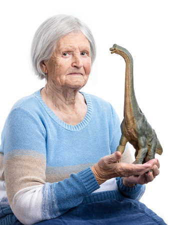 aging concept: Portrait of a senior woman holding a toy dinosaur over white background, aging concept, humorous aspect