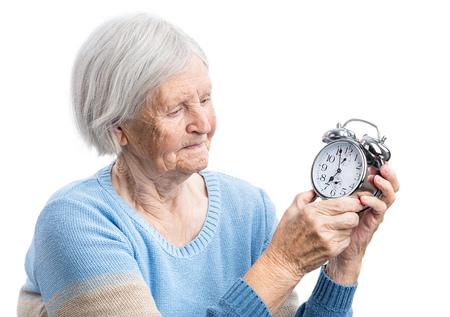 adult 80s: Senior woman holding a clock