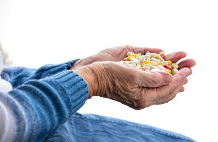 hand holding pills: Cropped view of senior woman holding handful of pills over white Stock Photo