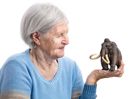 aging: Portrait of a senior woman holding a toy mammoth over white background, aging concept, humorous aspect