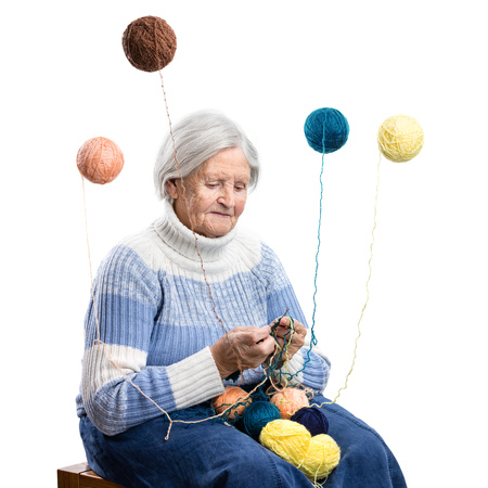 wools: Senior woman knitting over white background, wool balls flying around, woman magician