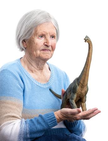 señora mayor: Retrato de una mujer mayor que sostiene un dinosaurio de juguete sobre fondo blanco, el concepto de envejecimiento, aspecto humorístico