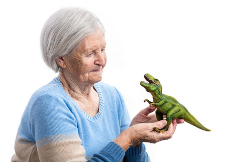 aging: Portrait of a senior woman holding a toy dinosaur over white background, aging concept, humorous aspect
