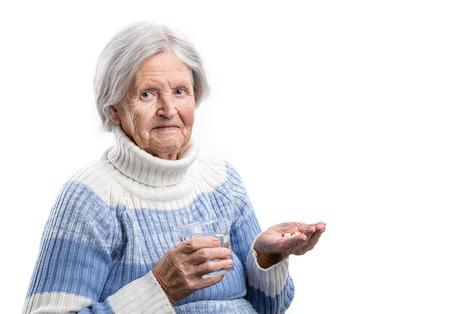 over white: Elderly woman taking her medication over white