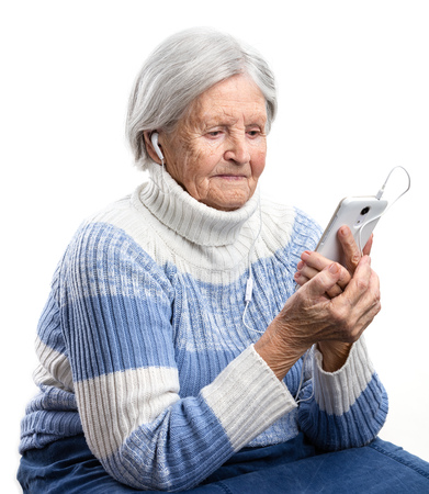 new age music: Senior woman listening to music or watching video on smartphone