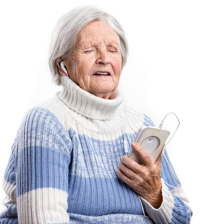 adult 80s: Senior woman listening to music and singing over white background