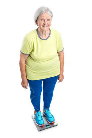 adult 80s: Senior woman weighing herself on scales over white background