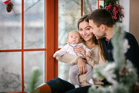 home decorated: Beautiful family with baby boy sitting near the window at home decorated for Christmas