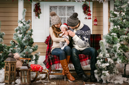 benches: Young family with a baby boy sitting on the bench in winter decorations Stock Photo