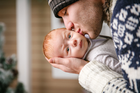 two face: Father holding and kissing baby son among while wearing winter hat, with Christmas tree in background Stock Photo