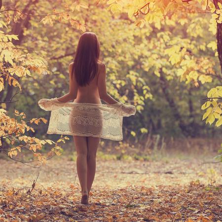 Красивая голая женщина в лесу в летний день