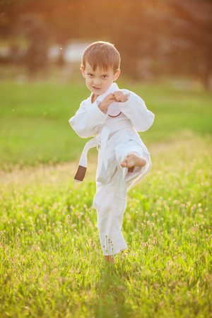 Preschool boy practicing karate outdoors photo