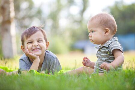 hermanos jugando: hermanos peque�os que juegan en la hierba en un parque Foto de archivo