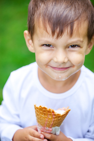 Portrait of young kid eating a tasty ice cream outdoor photo
