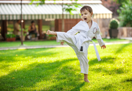 Preschool boy practicing karate outdoors Imagens