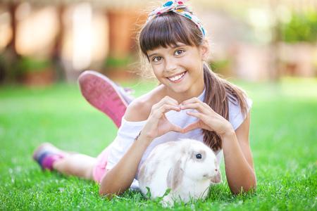 silhouette lapin: Sourire fille montrant un signe de coeur avec ses mains sur un lapin Banque d'images