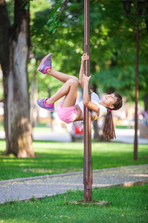lamp on the pole: Cute girl having fun outdoor using a street lamp as a gymnastic pole Stock Photo