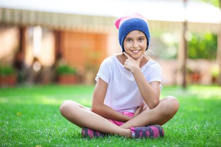niña alegre que se sienta en la hierba