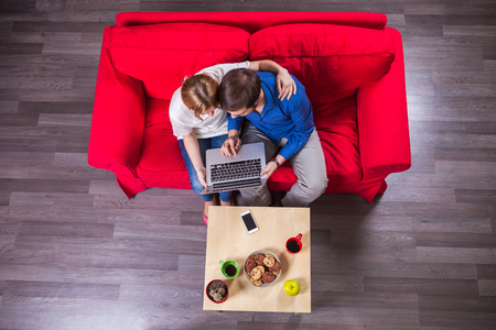couple on couch: Young couple using laptop while sitting on couch