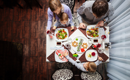 mom and dad: Family of four having meal at a restaurant