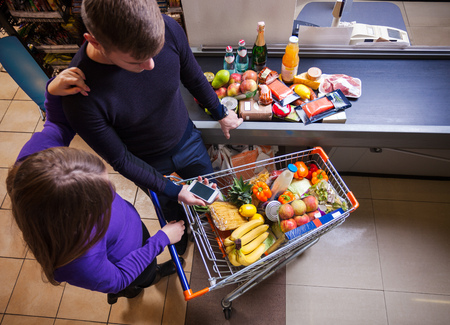 checkout: Young couple before checkout in supermarket Stock Photo