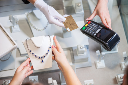 pagando: Joven comprar un collar de oro con piedras preciosas azules y pagar con una tarjeta de crédito