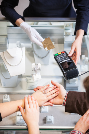 pagando: Young woman buying a golden ring and paying with a credit card