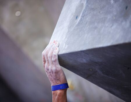 handhold: Closeup of mans hand on handhold on artificial climbing wall, hand in focus
