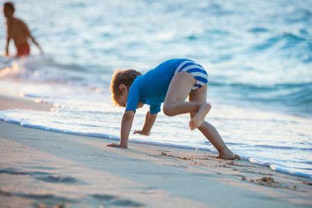 Niño feliz jugando en la playa.