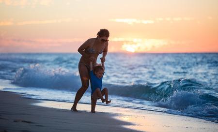 Moeder en zoon met plezier op het strand bij zonsondergang