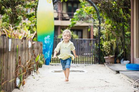 pies descalzos: El muchacho rubio lindo que recorre descalzo en el centro turístico tropical