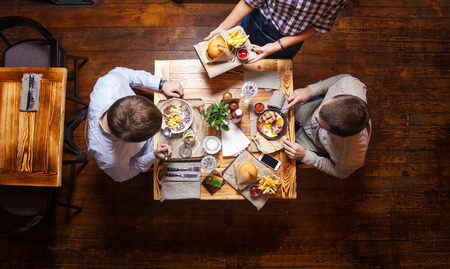 Young men having lunch at a cafe, view from above