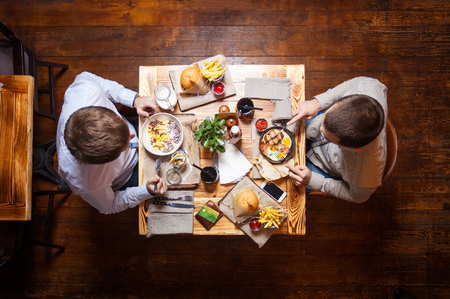 restaurant dining: Young men eating out in cafe or restaurant