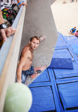 handhold: Male climber before jump on top handhold on artificial climbing wall