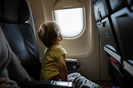 asiento: Niño pequeño que mira fuera de la ventana de avión Foto de archivo