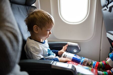 reading magazine: Little boy reading magazine on airplane