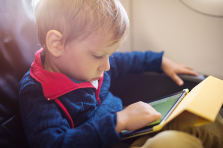 boys playing: Little boy using tablet on board of aircraft Stock Photo