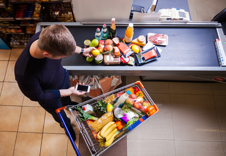 Young man before checkout in supermarket