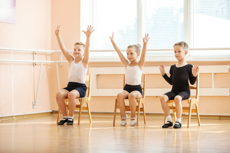 arms on chair: Young dancers playing or doing exercise while sitting on chairs at ballet class