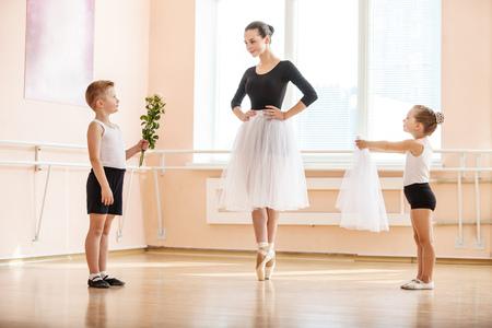 niñas pequeñas: En el ballet clase de baile: niño y una niña que da las flores y velo para estudiante de más edad, mientras que ella está bailando en punta
