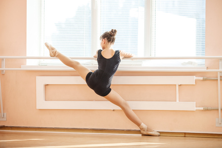 'ballet girl': Young girl doing splits while warming up at ballet dance class Stock Photo