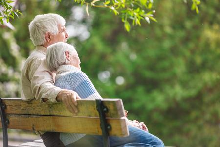 高齢者のカップルが公園のベンチで休んで