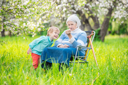 grandkid: Senior woman showing something in hand to great grandson while relaxing in blossoming orchard