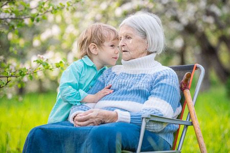the great grandmother: Little boy telling a secret to his great grandmother in a blossoming orchard