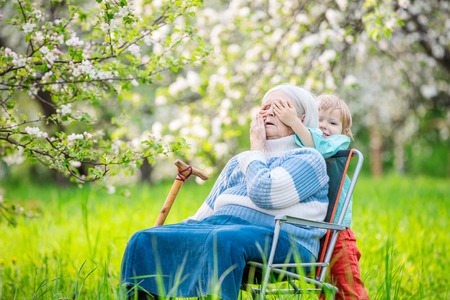 the great grandmother: Little boy playing peekaboo with his great grandmother