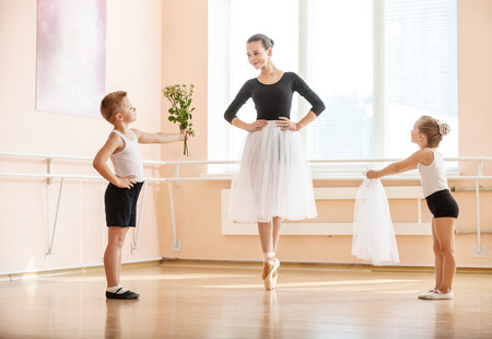 At ballet dancing class: young boy and girl giving flowers and veil to older student while she is dancing en pointe Stock Photo