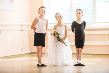 At ballet dancing class: young boys and a girl with flowers posing gracefully
