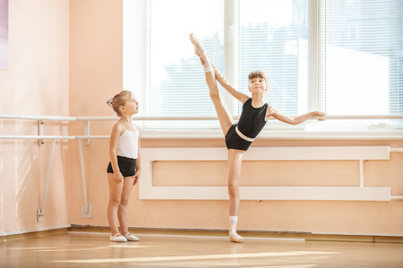 Little girl watching older ballet student practicing at barre Stock Photo